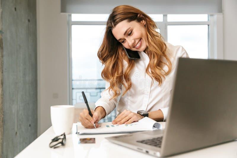 Donna di affari vestita in camicia convenzionale dei vestiti all'interno che parla dal telefono cellulare facendo uso delle note  immagini stock