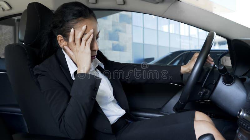 Donna di affari in vestito che si siede in auto, ritenendo malato e stanco, sintomi dei pms fotografia stock