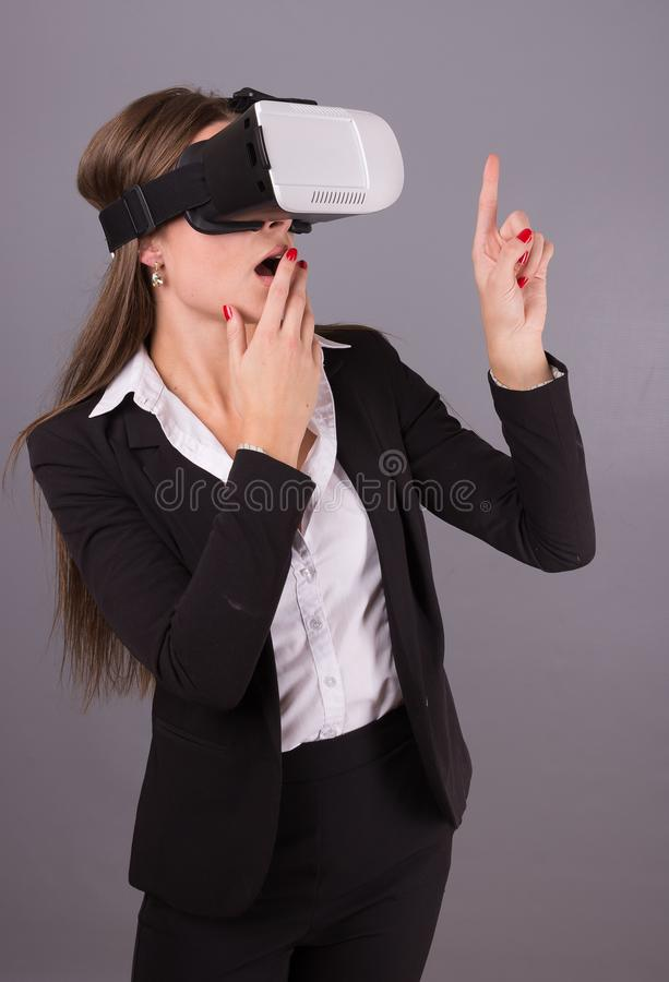 Donna di affari in vetri portabili di tecnologia VR Giovane donna sicura in un vestito in cuffia avricolare di realtà virtuale fotografia stock libera da diritti