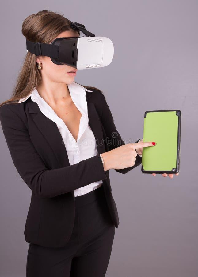 Donna di affari in vetri portabili di tecnologia VR Giovane donna sicura in un vestito in cuffia avricolare di realtà virtuale fotografie stock