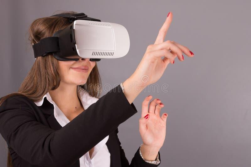 Donna di affari in vetri portabili di tecnologia VR Giovane donna sicura in un vestito in cuffia avricolare di realtà virtuale immagini stock