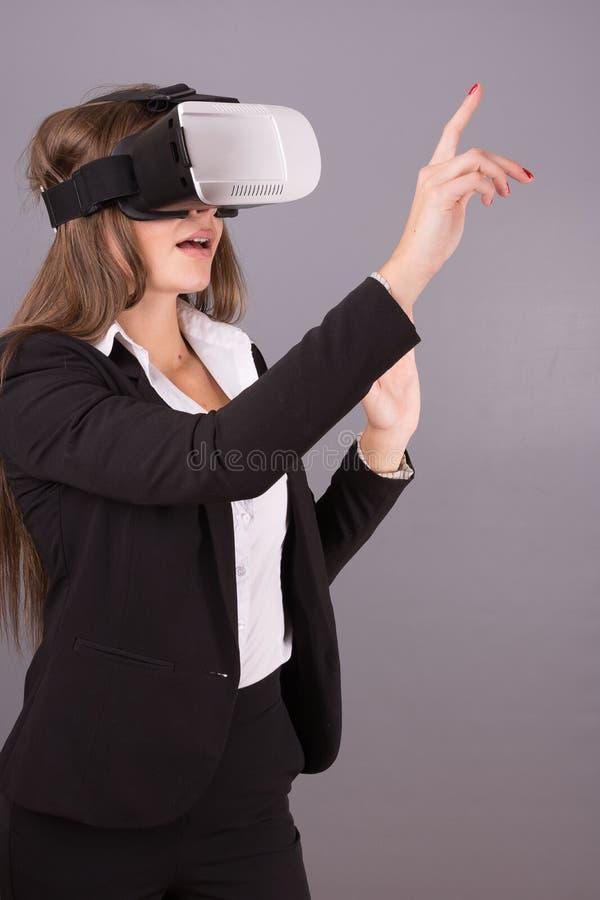 Donna di affari in vetri portabili di tecnologia VR Giovane donna sicura in un vestito in cuffia avricolare di realtà virtuale immagini stock libere da diritti