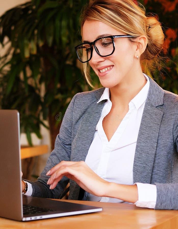 Donna di affari Working On Laptop in caffetteria Giovane affare w immagini stock