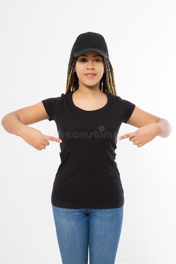 Donna di afro in maglietta nera e berretto da baseball del modello isolati su fondo bianco Cappello e maglietta in bianco di spor immagini stock libere da diritti