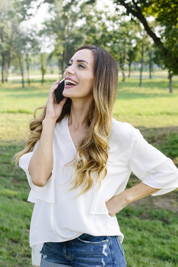 Donna di Attrractive che utilizza telefono cellulare nel parco immagine stock libera da diritti