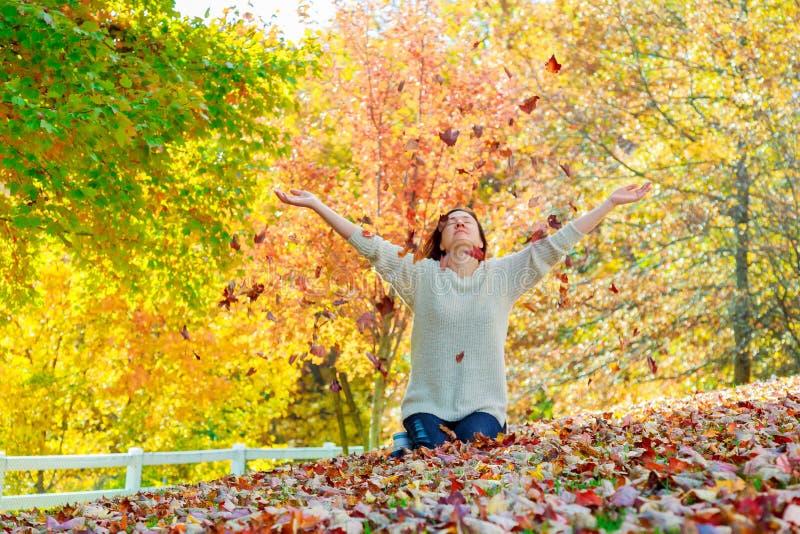 Donna di autunno sulla priorità bassa dei fogli fotografie stock