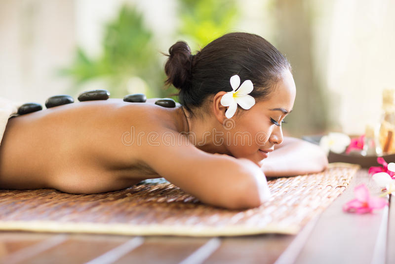 Donna di balinese che ha massaggio di pietra caldo nel salone della stazione termale immagini stock