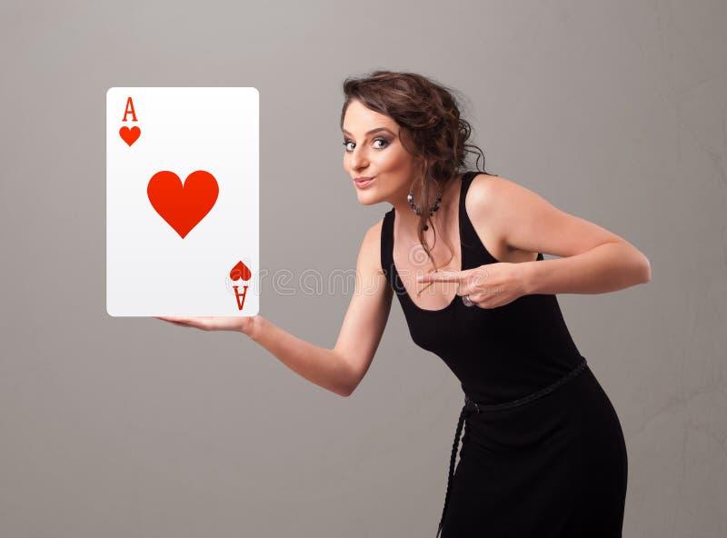 Donna di Beautifu che tiene un asso rosso del cuore immagini stock