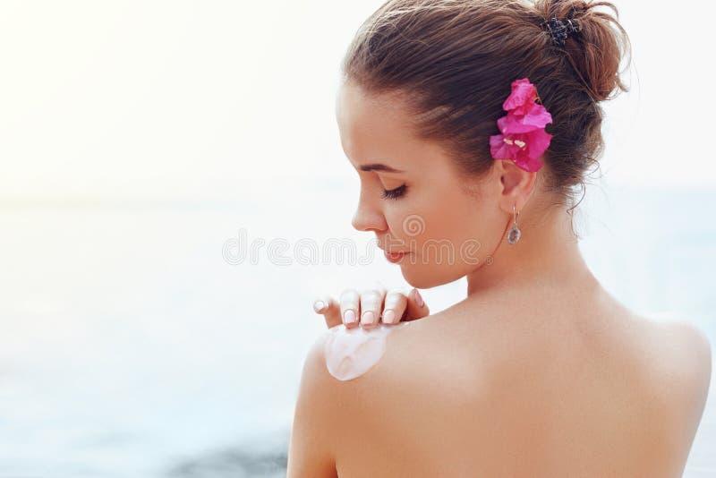 Donna di bellezza che applica la crema della protezione solare sulla spalla abbronzata Skincare Crema del sole di protezione di S fotografia stock