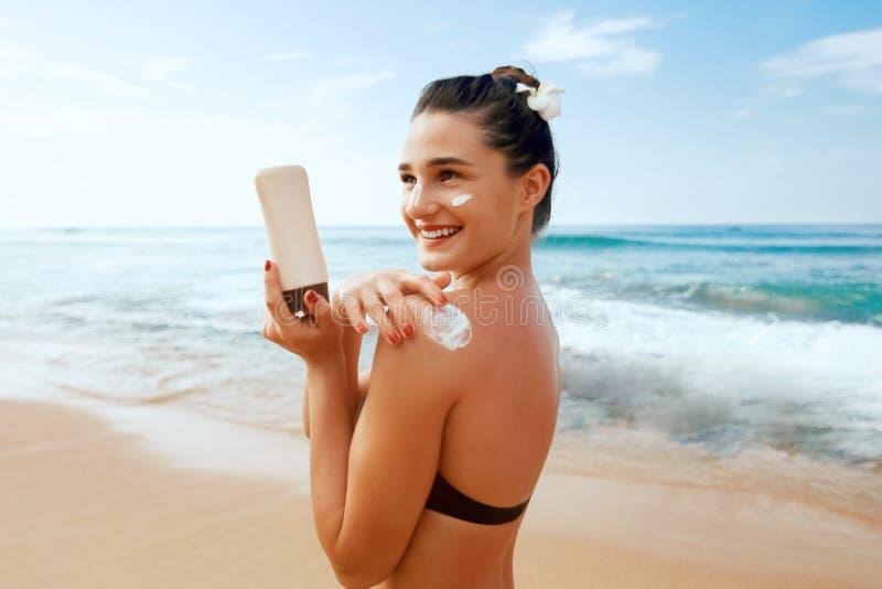 Donna di bellezza che applica la crema della protezione solare sulla spalla abbronzata Skincare Suncream di protezione di Sun del immagini stock