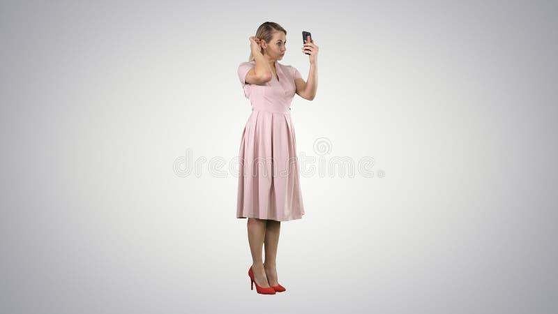 Donna di bellezza che la esamina in suo smartphone che ripara i suoi capelli sul fondo di pendenza fotografia stock libera da diritti