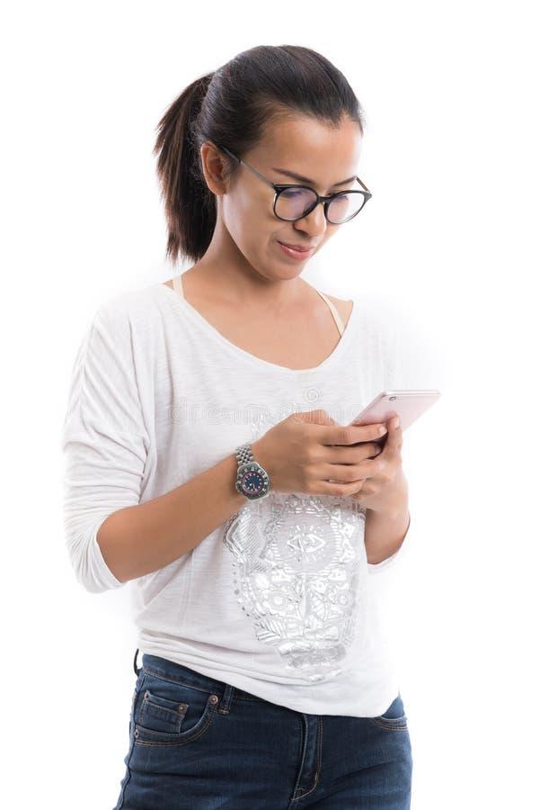 Donna di bellezza che per mezzo di un telefono cellulare isolato su un fondo bianco immagini stock
