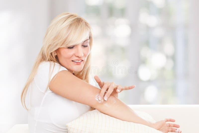 Donna di bellezza che usando crema d'idratazione fotografie stock libere da diritti
