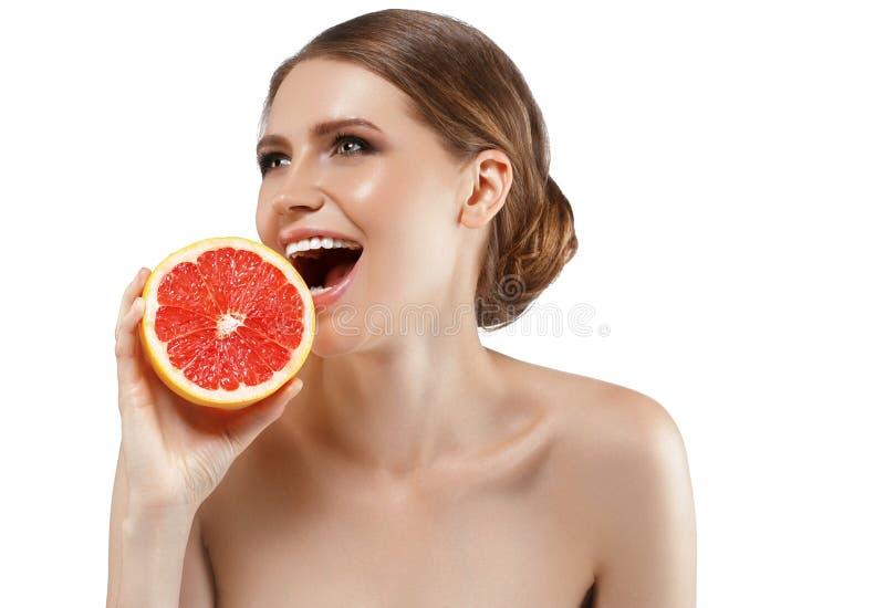 Donna di bellezza con il pompelmo arancio dell'agrume con la domanda biologica di ossigeno sana della pelle fotografia stock