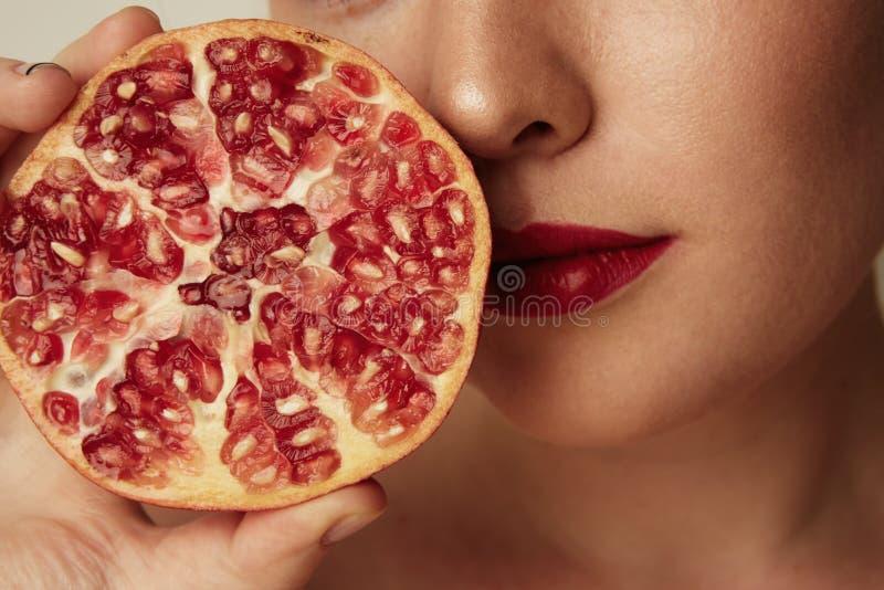 Donna di bellezza con il taglio arancio del melograno a metà sopra fondo bianco Concetto fresco attraente della vitamina Colpo de fotografie stock