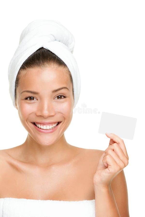 Donna di bellezza della stazione termale che mostra biglietto da visita immagini stock