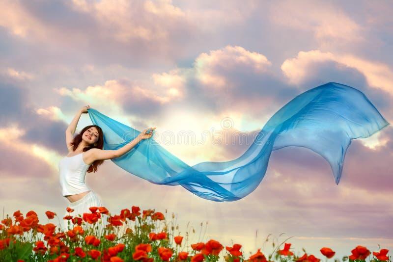 Donna di bellezza nel campo del papavero con il tessuto immagini stock
