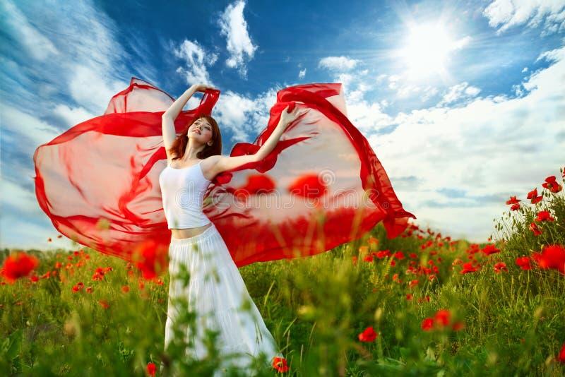 Donna di bellezza nel campo del papavero con il tessuto fotografie stock libere da diritti