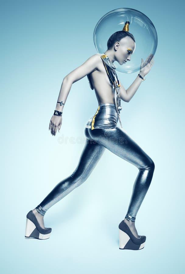 Donna di camminata del cyborg in vestito ed in casco d'argento fotografia stock