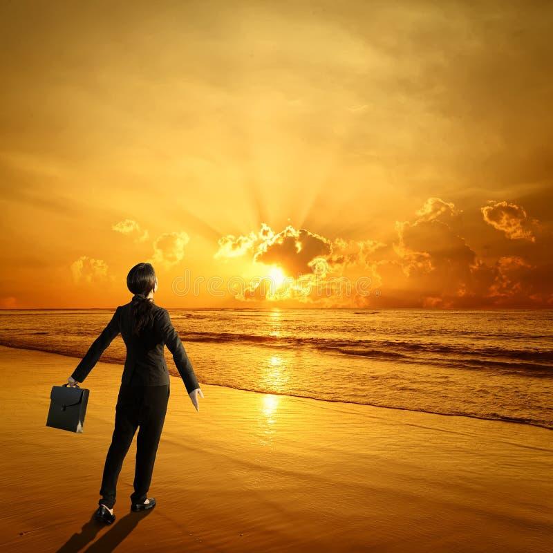 Donna di camminata di affari che tiene una cartella sulla spiaggia e sul tramonto immagine stock