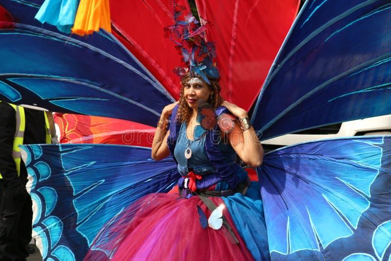 Donna di carnevale di Notting Hill che porta il costume variopinto dell'ala della farfalla immagini stock