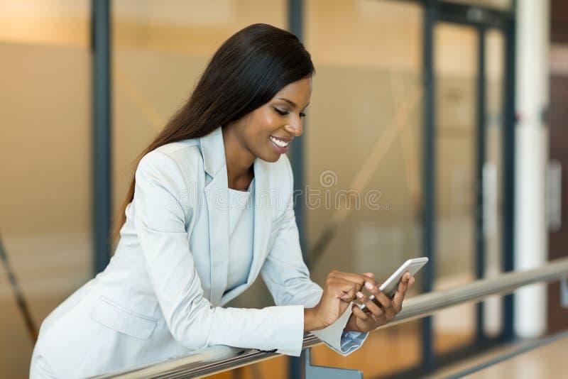 donna di carriera che per mezzo del telefono immagine stock