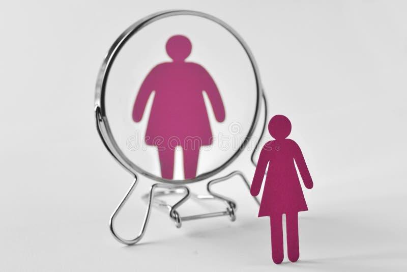 Donna di carta esile che guarda nello specchio e che si vede come donna grassa - anoressia e concetto di disordini alimentari immagini stock libere da diritti