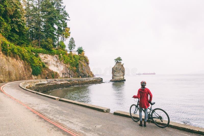 Donna di ciclismo del ciclista di Vancouver sul percorso della bici intorno a Stanley Park, attività turistica famosa in Columbia fotografie stock libere da diritti