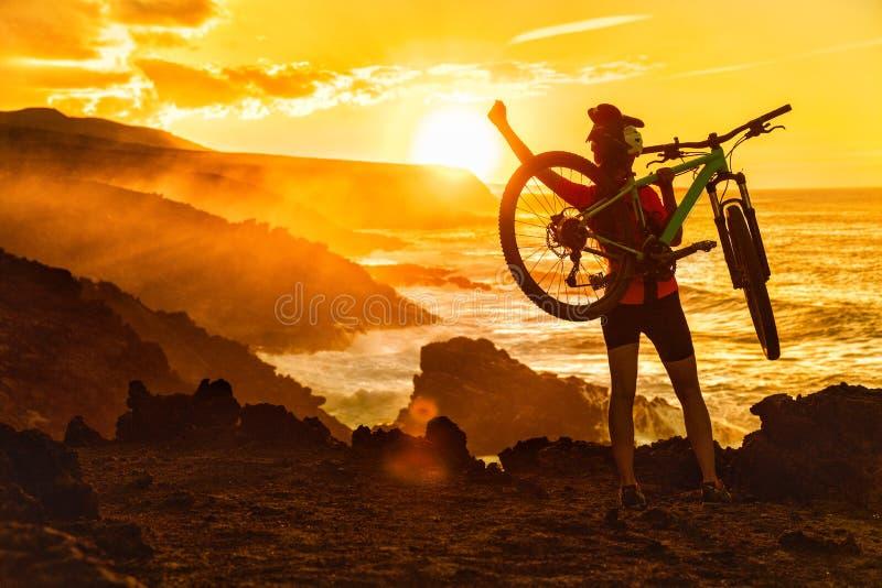 Donna di ciclismo di montagna di successo MTB al tramonto della natura fotografia stock