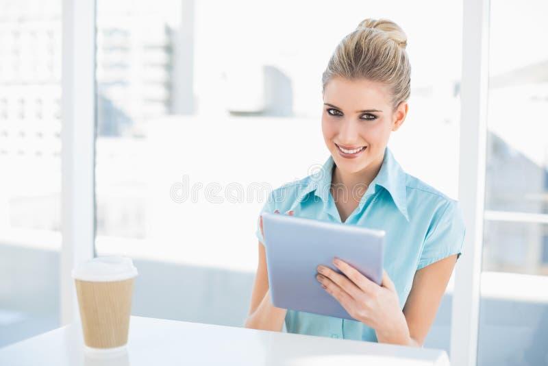 Donna di classe allegra che per mezzo della compressa mentre avendo una rottura fotografie stock