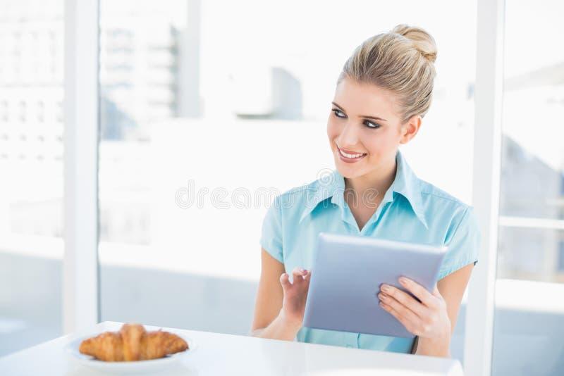 Donna di classe allegra che per mezzo della compressa mentre mangiando prima colazione fotografia stock libera da diritti