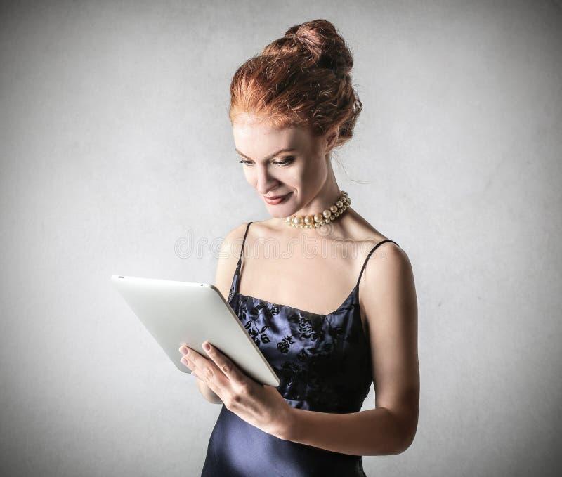 Donna di classe che per mezzo di una compressa fotografie stock