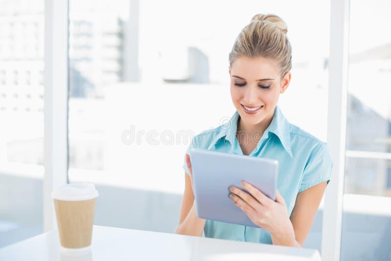Donna di classe sorridente che per mezzo della compressa mentre avendo una rottura immagine stock libera da diritti