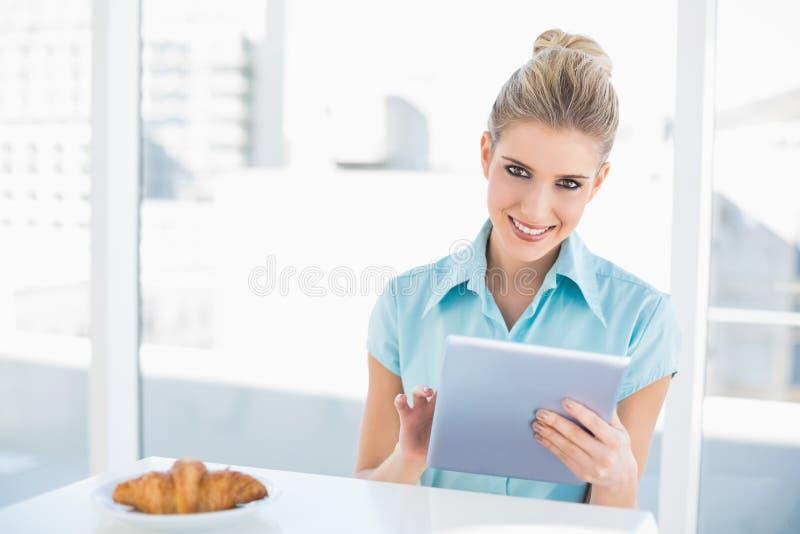 Donna di classe sorridente che per mezzo della compressa mentre mangiando prima colazione fotografie stock