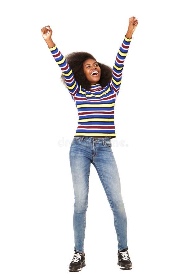 Donna di colore allegra dell'ente completo giovane che incoraggia con le armi alzate contro fondo bianco isolato immagine stock libera da diritti