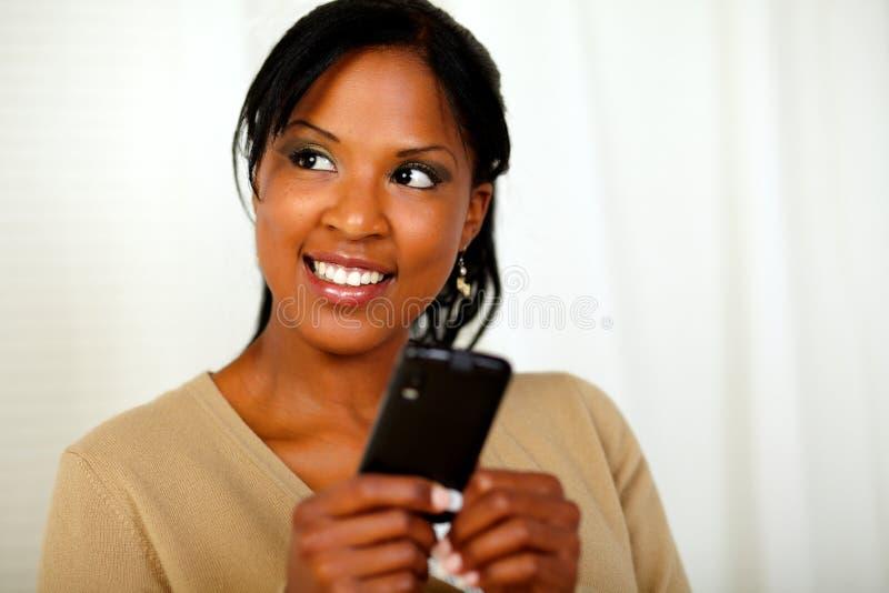 Donna di colore amichevole che trasmette un messaggio fotografie stock libere da diritti