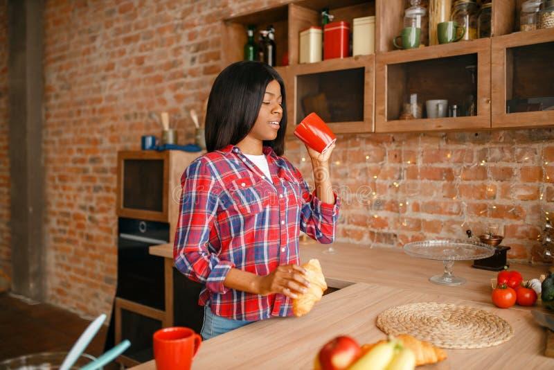 Donna di colore che cucina prima colazione sana sulla cucina fotografia stock libera da diritti