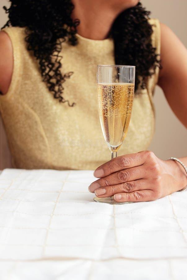 Donna di colore che giudica di vetro in pieno di champagne immagini stock libere da diritti