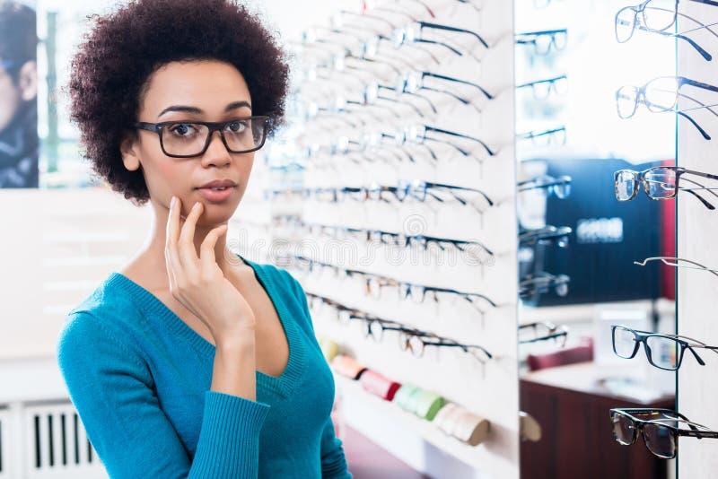 Donna di colore che prova sui vetri nel deposito dell'ottico immagine stock libera da diritti