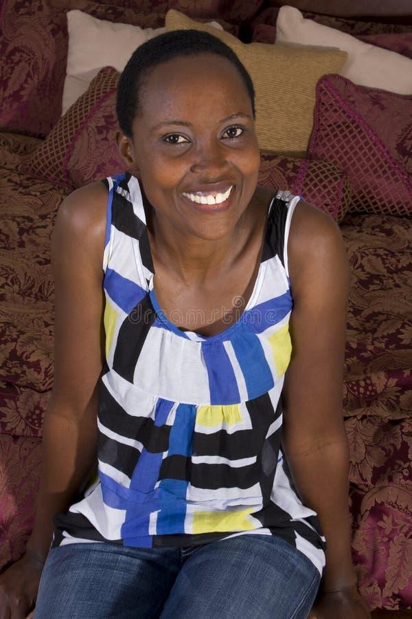 Donna di colore che si siede sulla base immagini stock