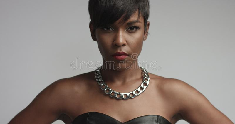 Donna di colore della corsa mista in vestito nero dal eather nel tiro dello studio fotografia stock libera da diritti