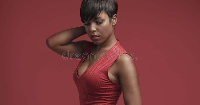 Donna di colore della corsa mista in vestito rosso che balla e che posa alla macchina fotografica fotografia stock libera da diritti