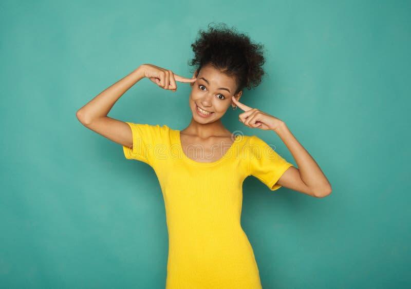 Donna di colore felice che indica alla sua testa immagini stock