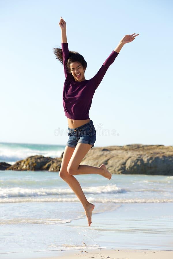 Donna di colore giovane allegra che salta dalla spiaggia immagine stock libera da diritti
