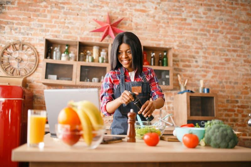 Donna di colore in grembiule che cucina prima colazione sana fotografia stock libera da diritti