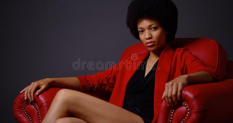 Donna di colore indipendente che si siede nella sedia rossa fotografia stock