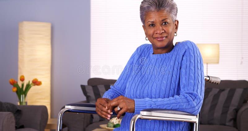 Donna di colore matura felice che si siede in sedia a rotelle immagini stock