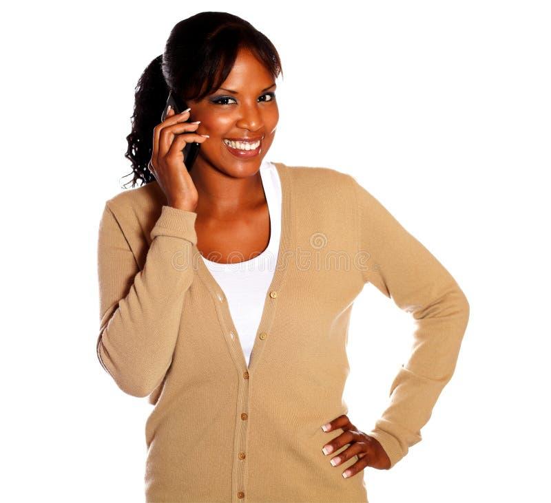Donna di colore sorridente che lo esamina mentre comunicando immagine stock libera da diritti