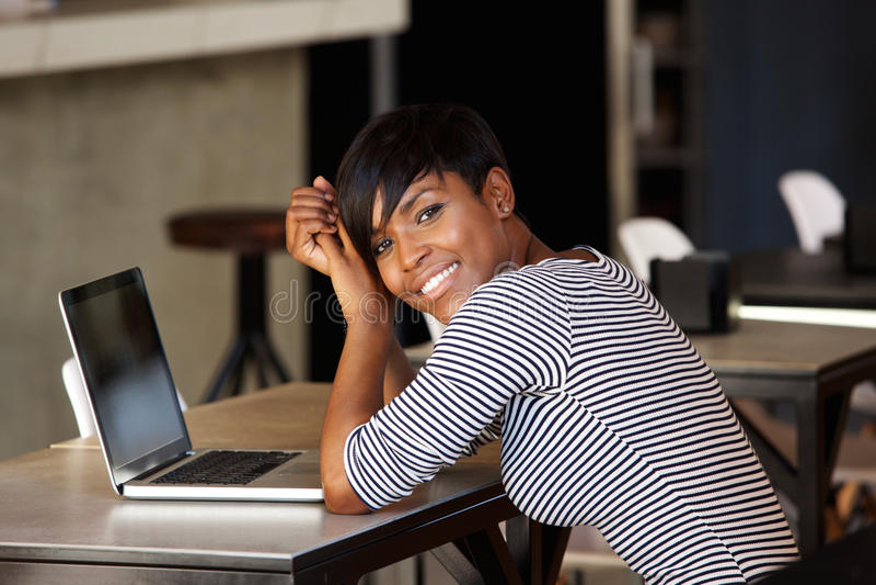 Donna di colore sorridente che si siede al caffè con il computer portatile fotografie stock libere da diritti