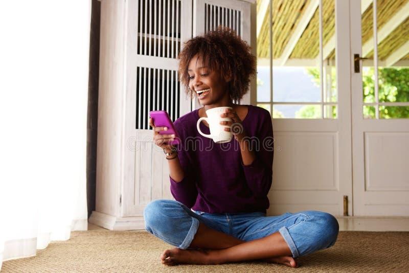 Donna di colore sorridente che si siede sul pavimento a casa con il telefono cellulare immagini stock